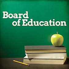 Board of Education written in white on green chalk board with books and green apple