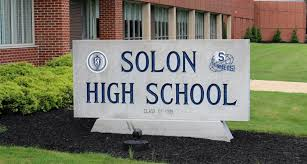 Front of Solon High School with grey stone sign reading Solon High School in blue letters