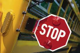 Close up of school bus with red stop sign