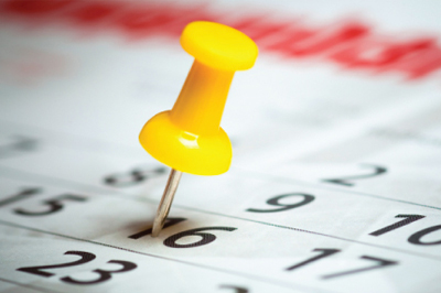 Close up of a yellow push pin marking a calendar page