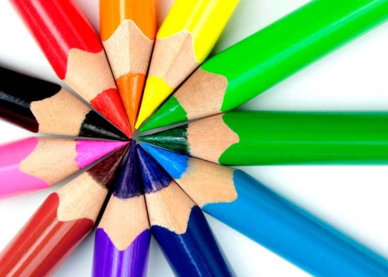 Rainbow colored pencils with points all facing inward in a flower shape